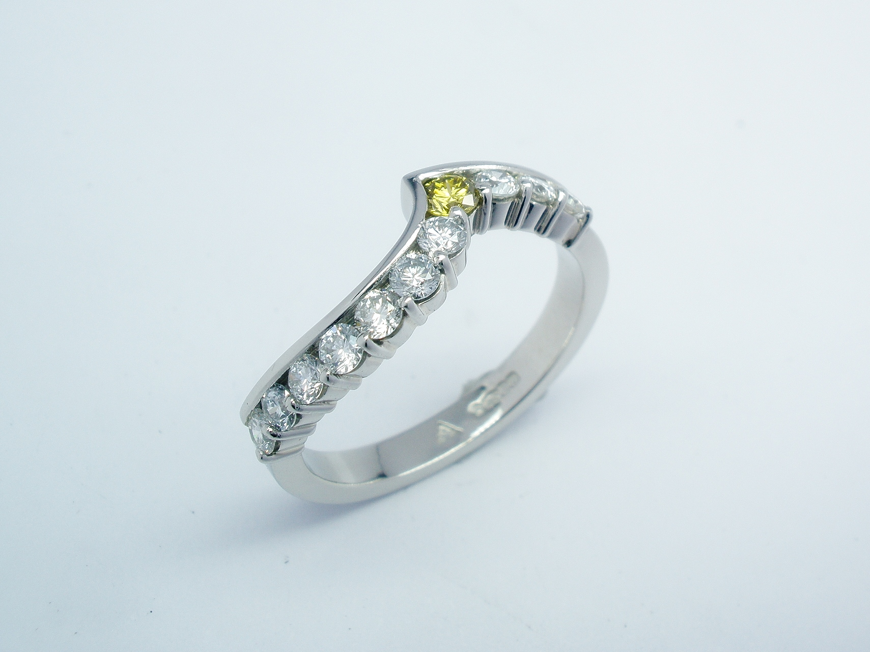 A platinum 11 stone canary yellow & white round brilliant cut diamond part channel set ring shaped to fit around a single stone diamond cross-over ring.