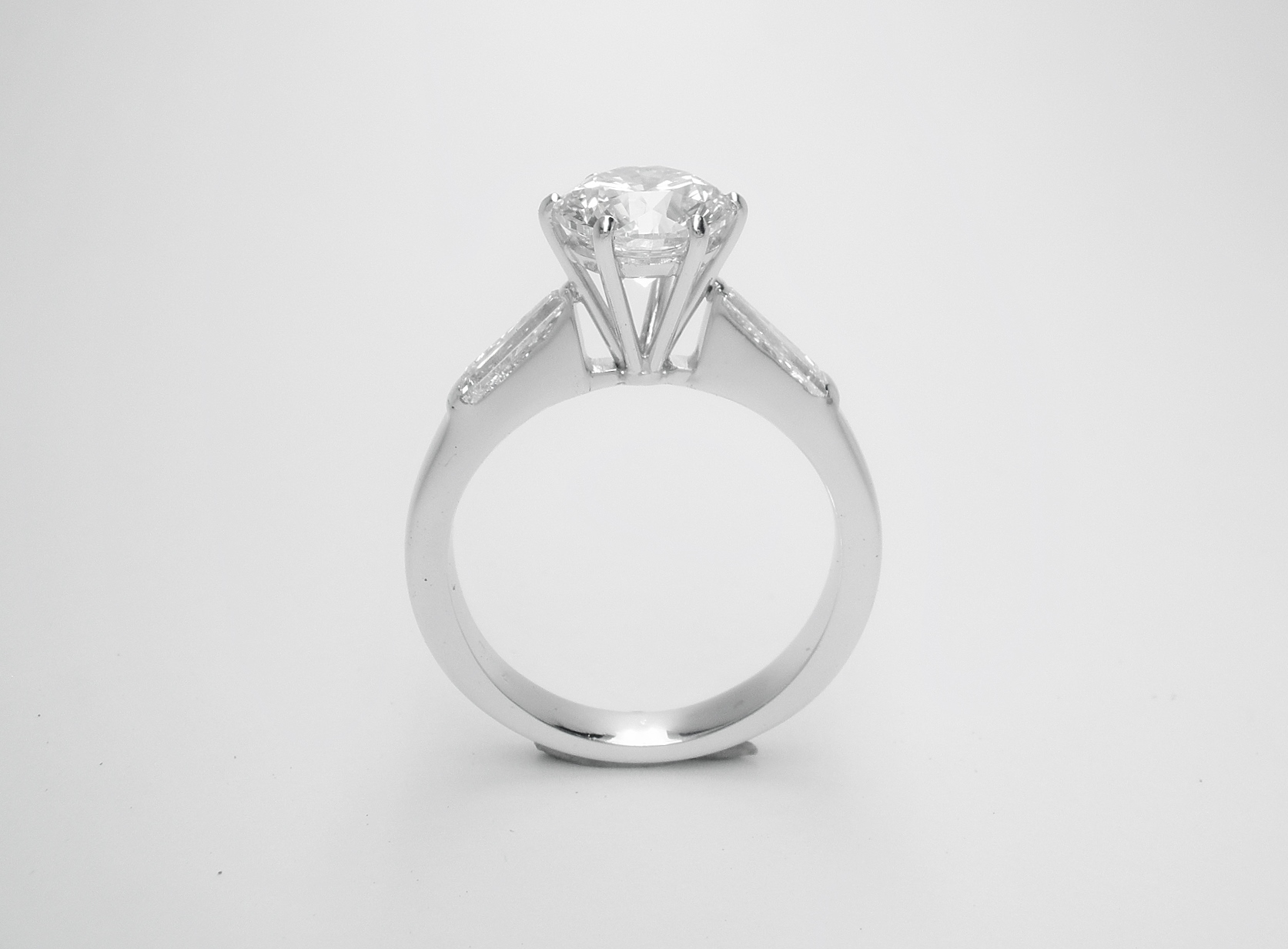 After The 1.50cts. round brilliant cut diamond set in a handmade higher platinum setting inserted successfully between the original tapered baguette shouldered 18ct white gold mount.