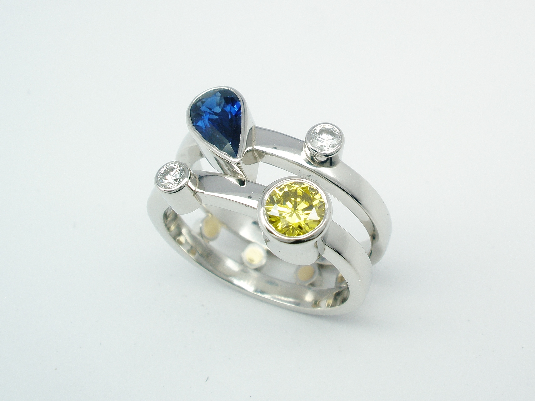 A platinum 4 stone pear sapphire, canary yellow & white round brilliant cut diamond twin parallel banded ring.