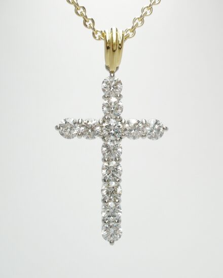 A 13 stone round brilliant cut diamond cross mounted in platinum & with an 18ct. yellow gold shackle.