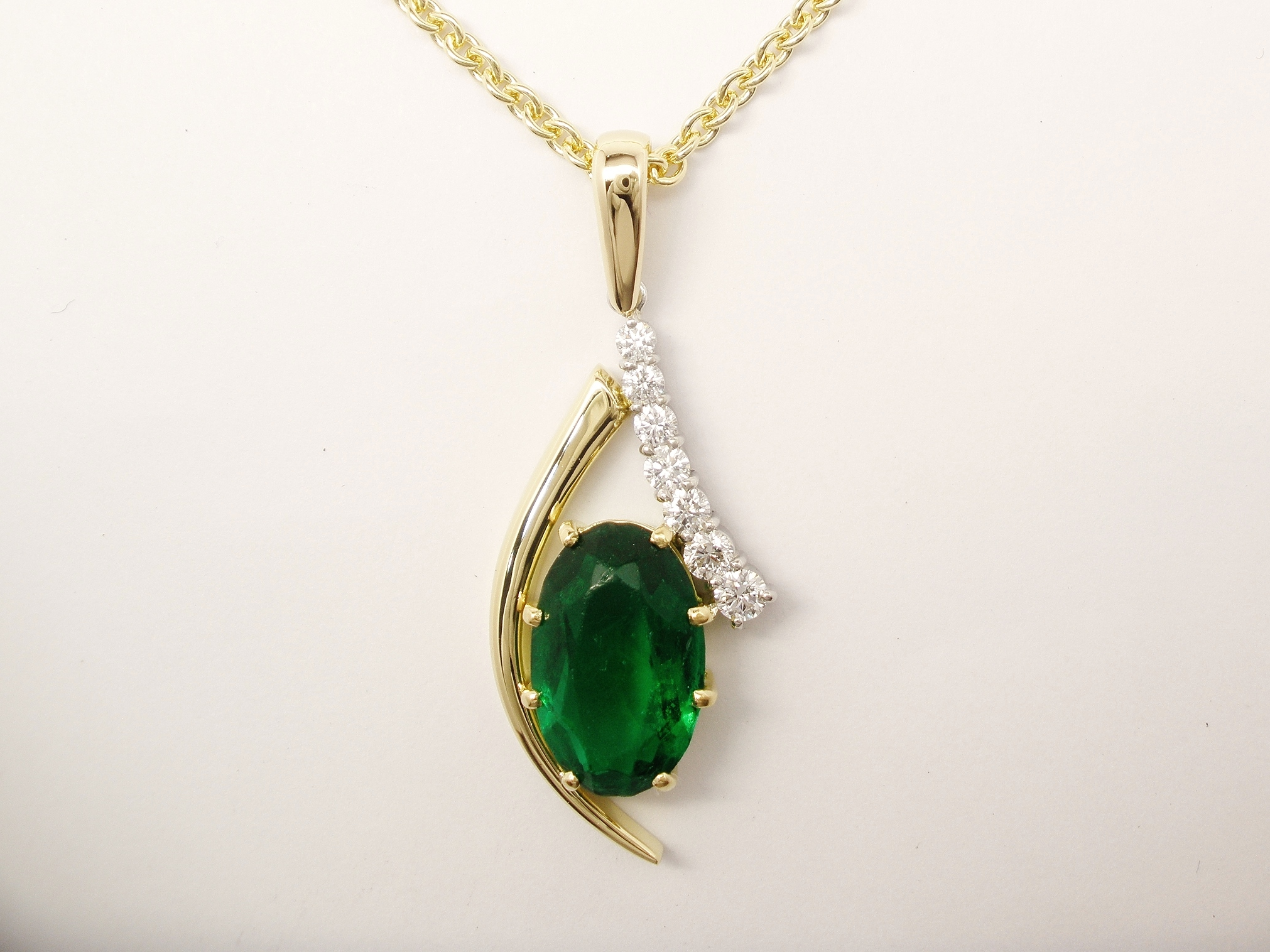 An 8 stone synthetic emerald and round brilliant cut diamond pendant mounted in 18ct yellow gold and platinum. The emerald was supplied by the client & sentimental to them.