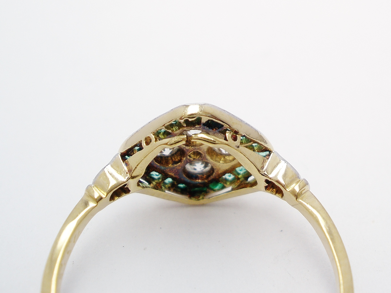 An emerald and diamond cluster, finely made in 18ct. yellow gold & topped in platinum very worn and broken on underside.