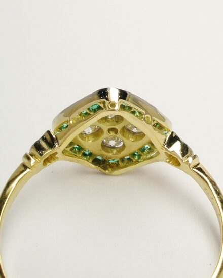 The 18ct. yellow gold back rail repaired and built up and the very fine platinum setting replaced & the emeralds reset.