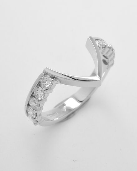 A 10 stone round brilliant cut part channel set platinum wedding ring with central 'V' wire to fit around a marquise cluster engagement ring.