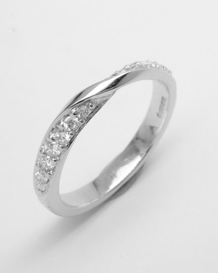 A platinum 14 tapering bead set round brilliant cut diamond cross-over style ring.