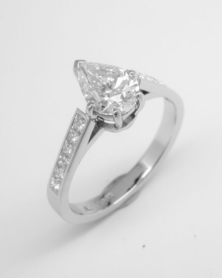 A single stone pear shaped diamond engagement ring mounted in platinum with 6 princess cut diamonds channel set in each shoulder.
