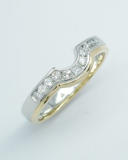 An 11 stone channel set round brilliant cut and princess cut diamond platinum and 18ct yellow gold shaped wedding ring.