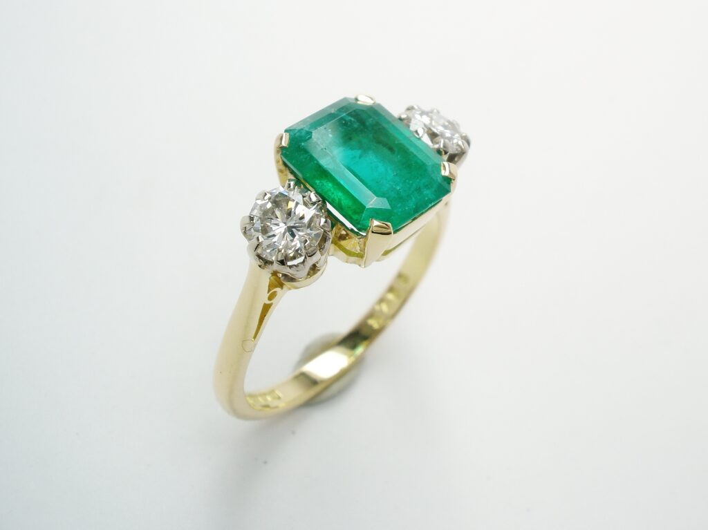 A 3 stone Octagonal emerald & round brilliant cut diamond ring. Replacing the emerald with a similar colour and clarity stone to the original. This stone had to be cut specially to fit the setting. The insurance covered the cost fully.