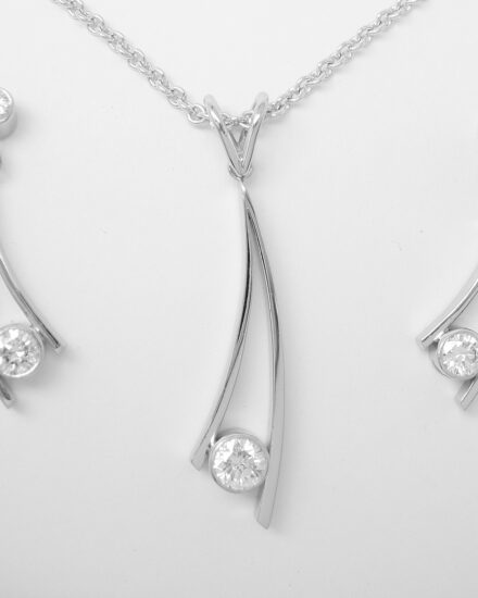 Single stone rub-over set round brilliant cut diamond curved wishbone style pendant & earring set mounted in platinum.