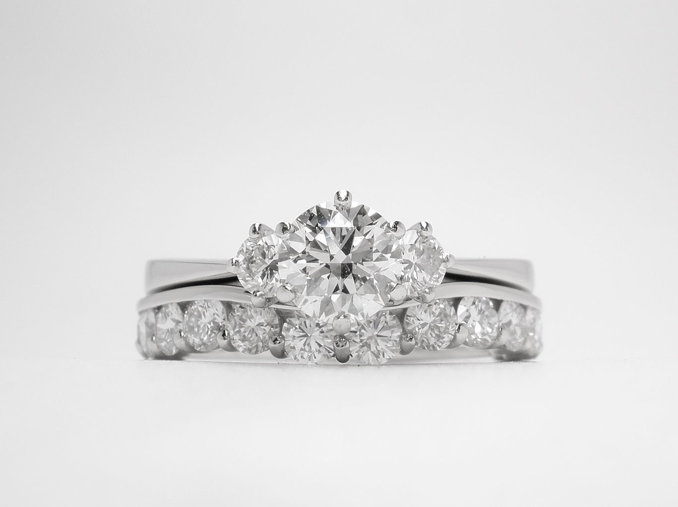 A 14 stone round brilliant cut part channel set eternity ring mounted in platinum and shaped to fit around a 3 stone diamond ring.