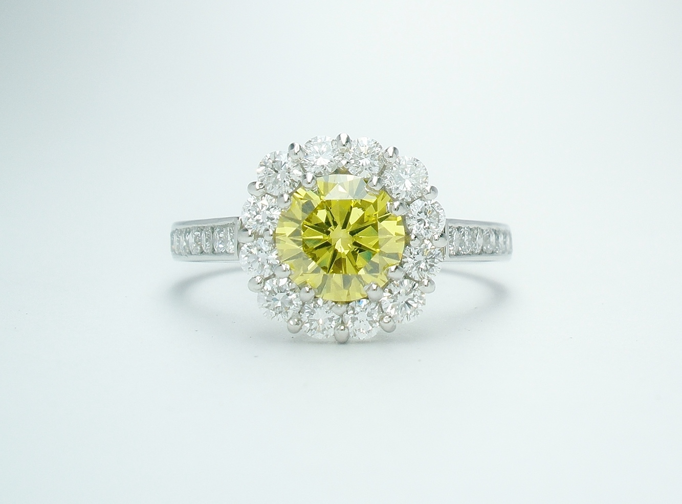 A 13 stone round brilliant cut 'HPHT' canary yellow diamond and white diamond round cluster with 7 round diamonds channel set down each shoulder.