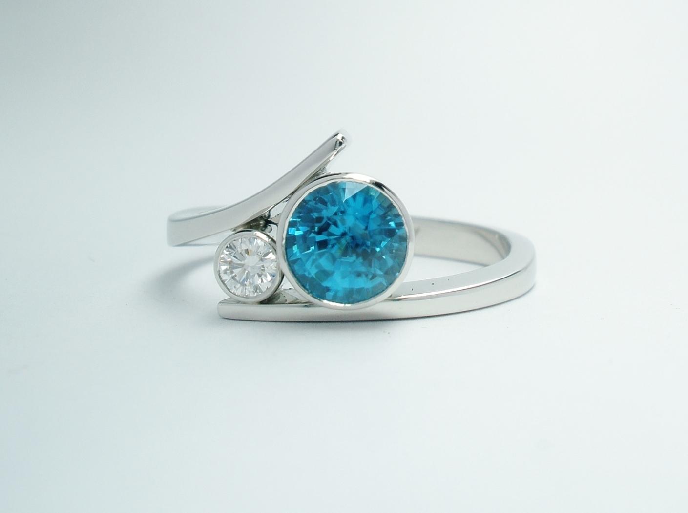 A platinum 2 stone rub-over set round blue Zircon and brilliant cut diamond straight wishbone cross-over dress ring.