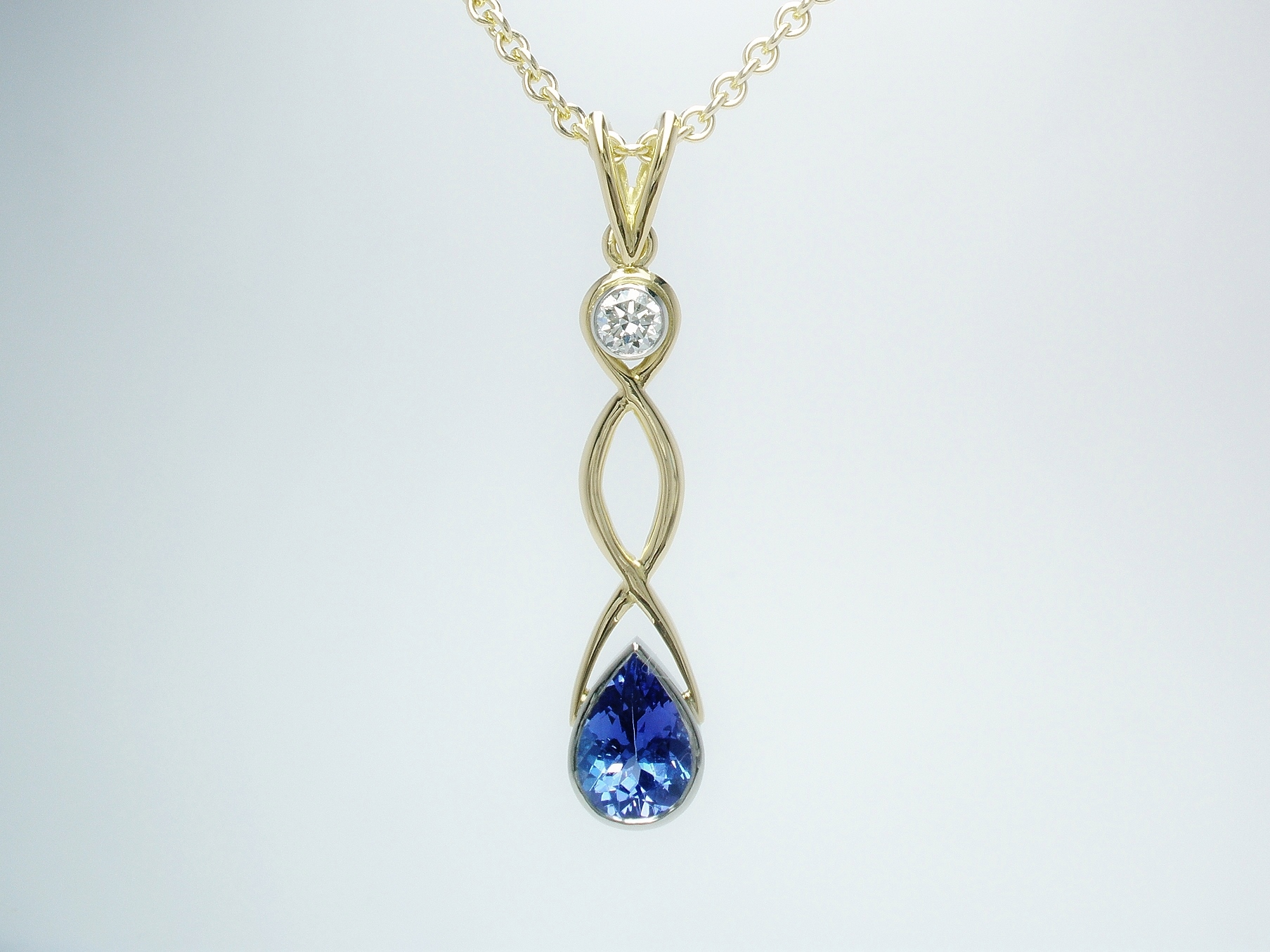 An 18ct. yellow gold hand carved Celtic style drop pendant mounted with a pear shaped tanzanite round brilliant cut diamond rub-over set in platinum.