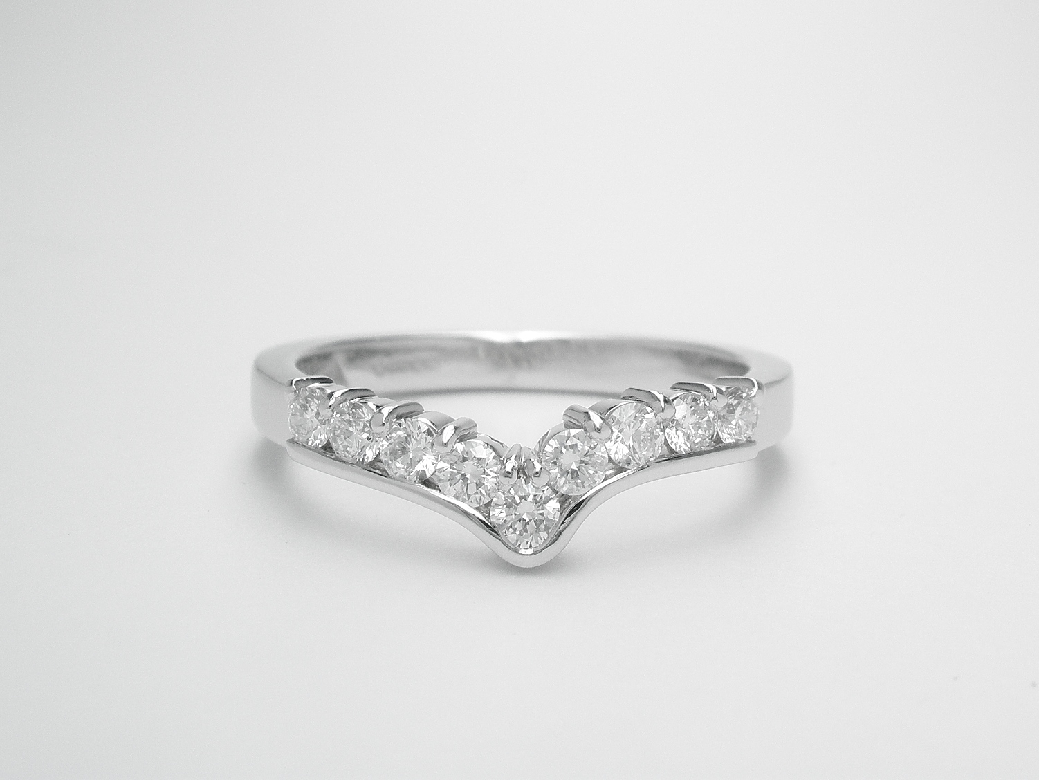 A 9 stone round brilliant cut diamond part channel set shaped eternity ring mounted in platinum.