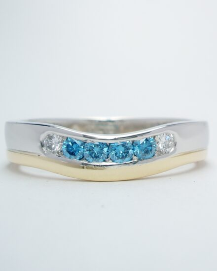 A platinum and 18ct. yellow gold wedding ring shaped to fit around a 3 stone diamond engagement ring and channel set with 4 sky blue & 2 white round brilliant cut diamonds.