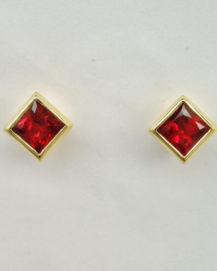 A pair of 3.5mm square princess cut super fine colour ruby earrings rub-over set in 18ct. yellow gold.
