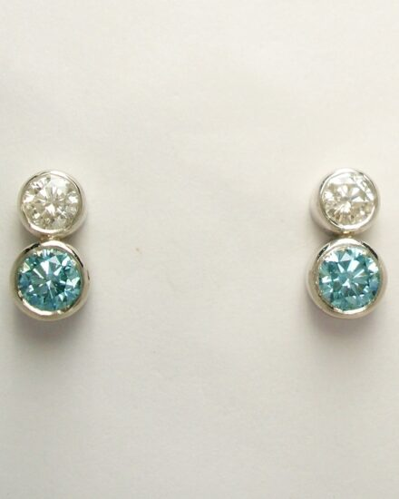 A pair of 2 stone sky blue and white diamond ear studs rub-over set in platinum to compliment the 5 stone pendant.