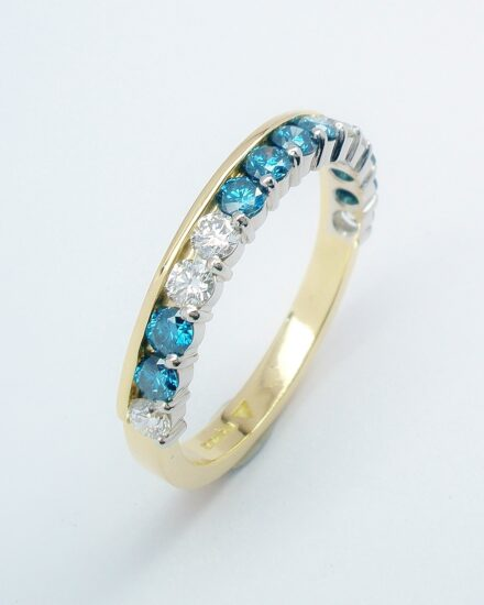 A 14 stone sky blue and white round brilliant cut part channel set ring mounted in 18ct. yellow gold and platinum.