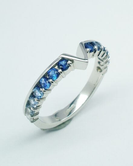 A platinum 14 stone round diamond cut sapphire and diamond part channel set ring shaped to fit around a marquise diamond and trillian cut 3 stone engagement ring.