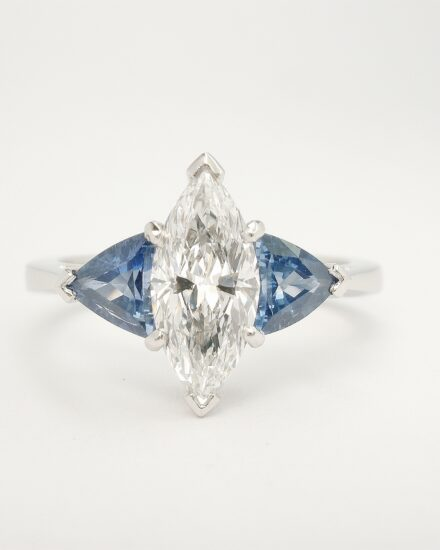 The 3 stone Marquise diamond and trilliant shaped sapphire ring mounted in platinum that has the 14 stone sapphire and diamond part channel set platinum ring shaped to fit.