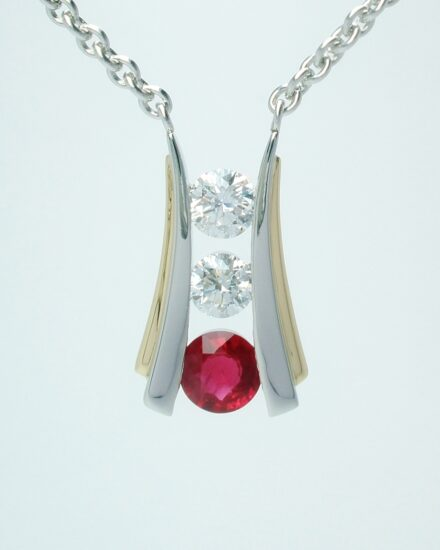 A 3 stone round ruby and round brilliant cut diamond pendant channel set in platinum and trimmed with 18ct. yellow gold.