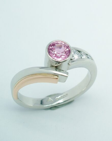 A round pink sapphire and diamond 4 stone wishbone cross-over style ring mounted in platinum and rose gold.