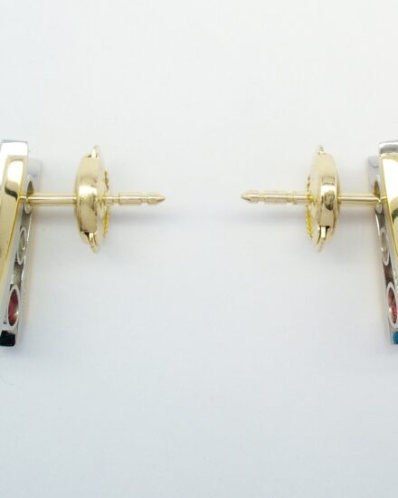 A pair of 3 stone round ruby and round brilliant cut diamond ear studs channel set in platinum, trimmed with 18ct. yellow gold and with 18ct. yellow gold 'guardian' safety fittings.