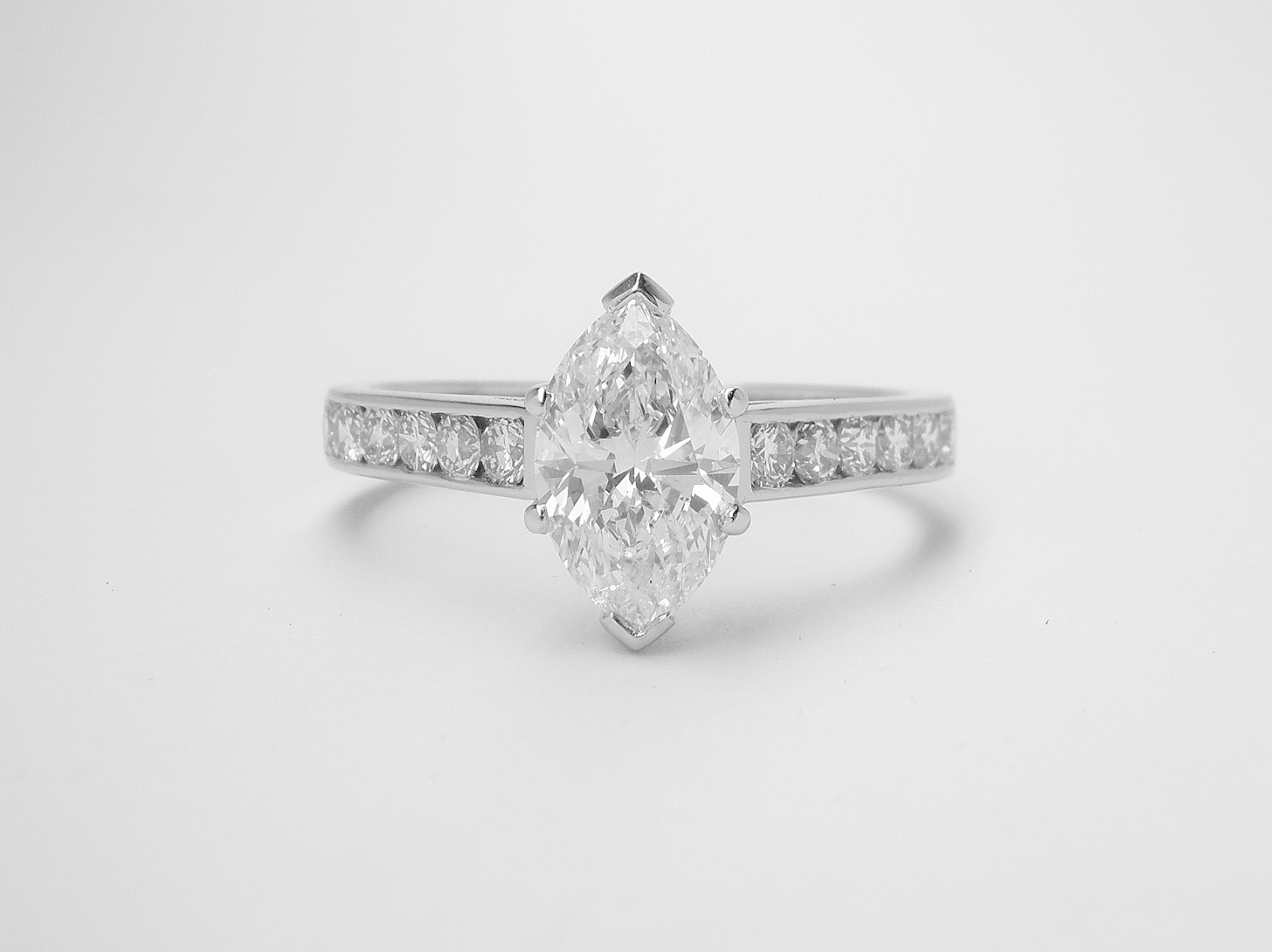A single stone marquise diamond ring mounted in platinum with 6 round brilliant cut diamonds channel set into each shoulder.
