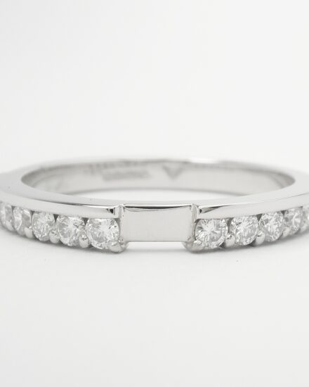 A 16 stone part channel set round brilliant cut diamond ring shaped to firt with a baguette and brilliant cut 3 stone engagement ring.