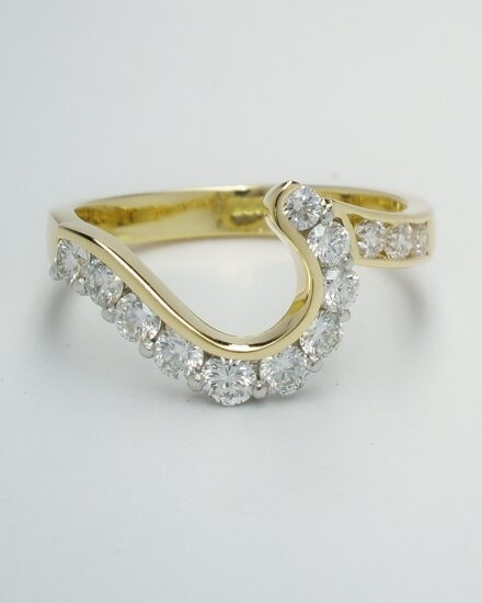 A 13 stone round brilliant cut diamond channel and part channel set ring mounted in 18ct. yellow gold and platinum and shaped to fit around a 2 stone cross-over engagement ring.