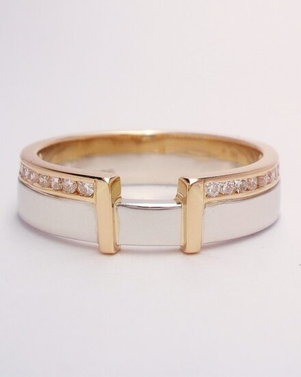A Platinum and 18ct. rose gold ring channel set with 20 small round brilliant cut diamonds and shaped to fit with a single stone radiant cut diamond ring.