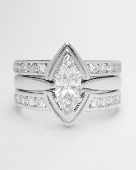 A pair of 10 stone channel set round brilliant cut diamond ring shaped with a central double 'V' wire to fit with a marquise diamond engagement ring.