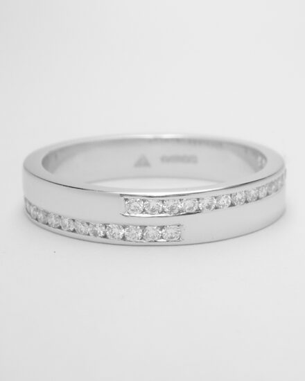 A platinum 32 stone double offset channel set round brilliant cut diamond ring with 3 diamonds on either side overlapping across the top.