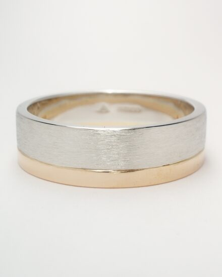 A 4.5mm broad platinum ring brushed finish with a 2mm broad red gold ring applied to one edge.