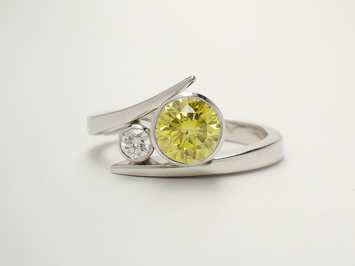 A 2 stone HPHT treated canary yellow and white round brilliant cut straight wishbone cross-over diamond ring. Mounted in platinum.