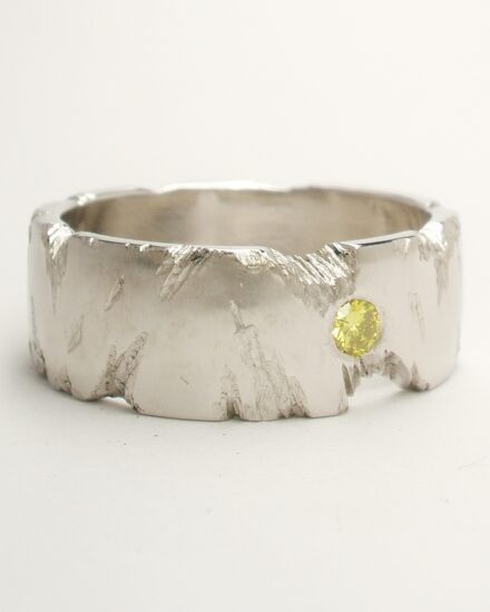 An 8mm broad platinum ring with fractured rock effect and flush set with a 2.8mm HTHP treated canary yellow diamond.