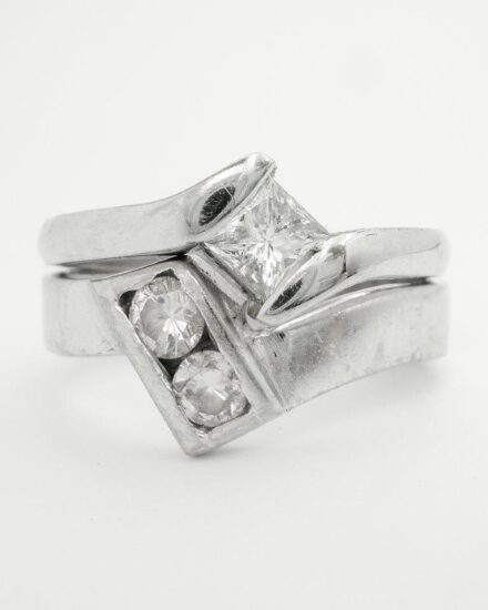 A 2 stone round brilliant cut diamond wedding ring to fit a single stone Princess cut cross-over engagement ring. Single stone princess cut diamond cross-over engagement ring. Very chunky & no finesse.