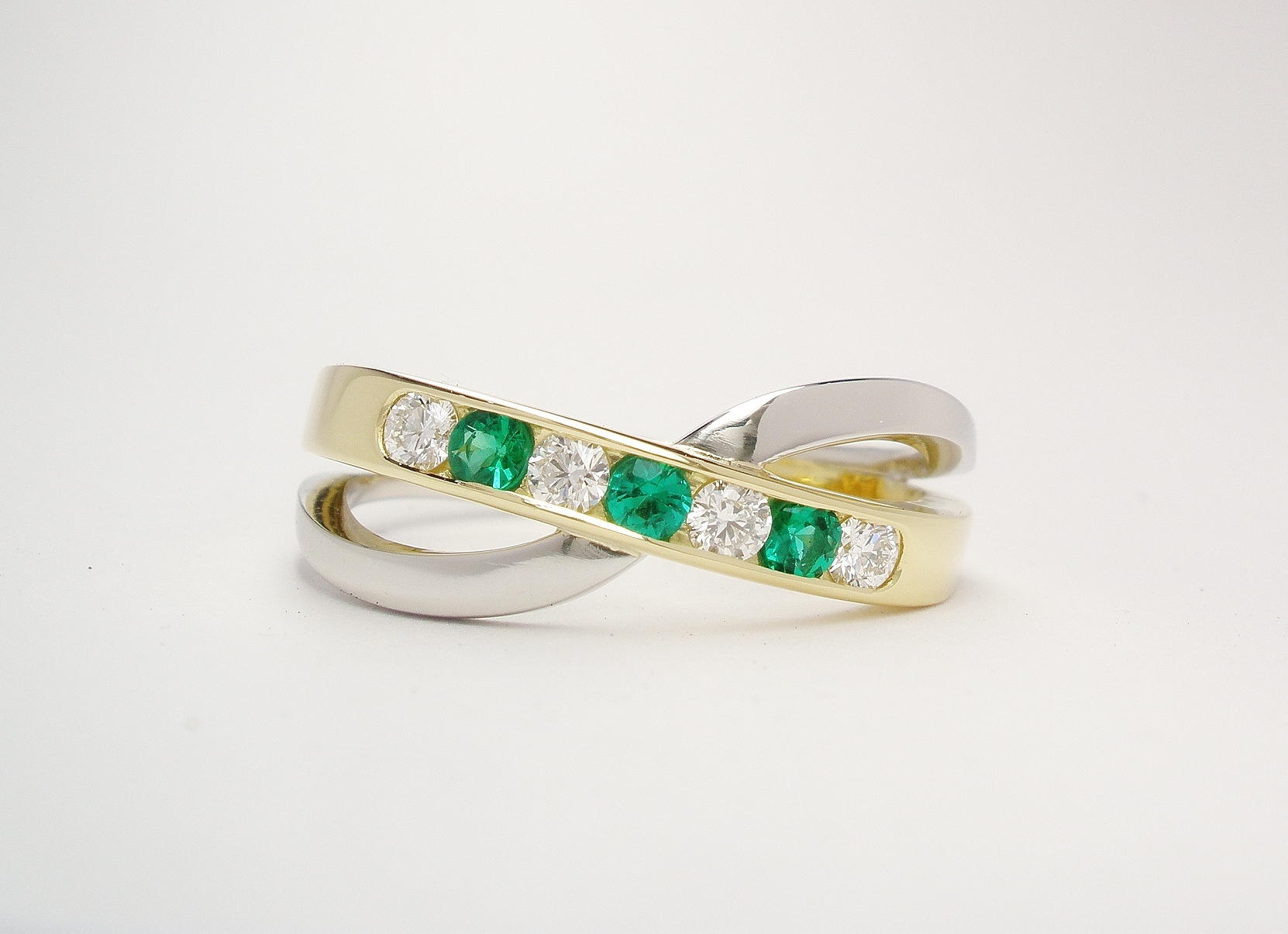 A 7 stone round brilliant cut diamond and emerald cross-over style ring mounted in 18ct. yellow gold and platinum.