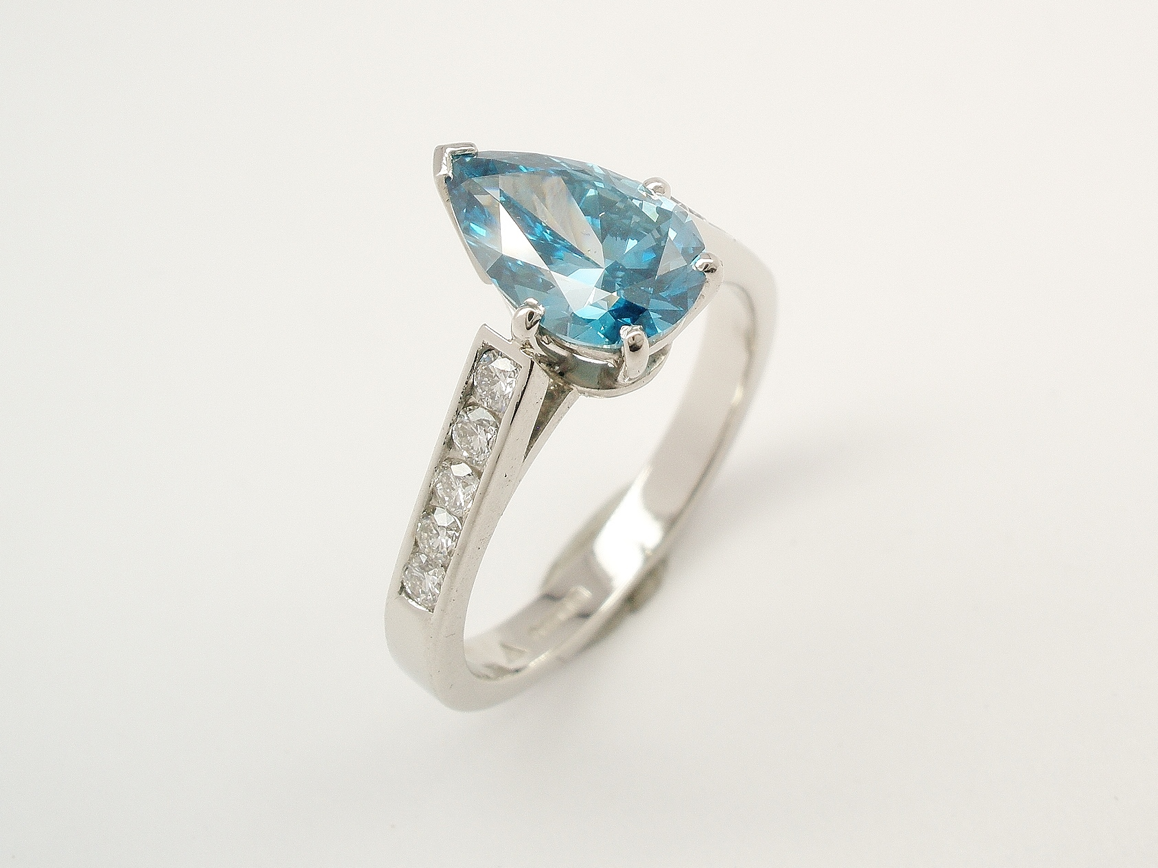 A single stone HTHP treated ocean blue pear shaped diamond ring mounted in platinum with channel set white round brilliant cut diamond shoulders.